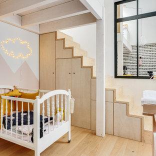 Idée de décoration pour une chambre de bébé fille design avec un mur rose, un sol en bois clair et un sol beige.