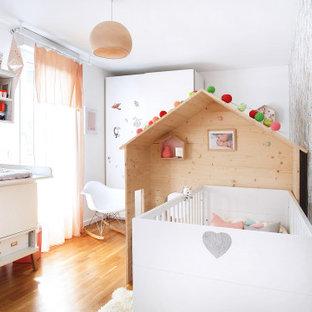 Cette photo montre une grand chambre de bébé fille tendance avec un mur multicolore, sol en stratifié, du papier peint, un sol marron et un plafond en papier peint.