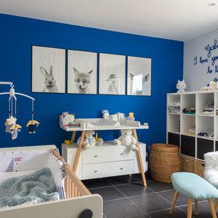 Immagine di una cameretta per neonati neutra minimal con pareti blu e pavimento grigio