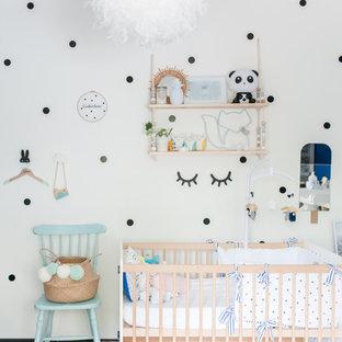 Idée de décoration pour une chambre de bébé design avec un mur blanc et un sol gris.
