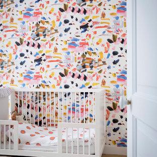 Cette image montre une chambre de bébé design avec un mur multicolore, un sol en bois clair et un sol beige.