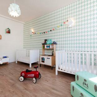 Réalisation d'une chambre de bébé neutre nordique avec un mur multicolore, un sol en bois clair et un sol beige.