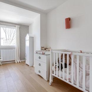 Cette image montre une chambre de bébé design avec un mur blanc, un sol en bois clair et un sol beige.