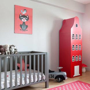 Exemple d'une chambre de bébé neutre scandinave de taille moyenne avec un mur gris, un sol en bois clair et un sol beige.