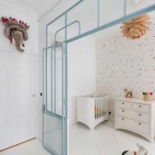 Cette image montre une chambre de bébé garçon nordique avec un mur multicolore et un sol blanc.