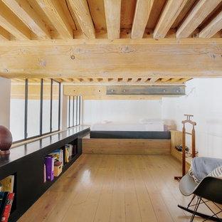 Cette image montre une chambre mansardée ou avec mezzanine urbaine avec un mur blanc, un sol en bois clair, aucune cheminée et un sol beige.