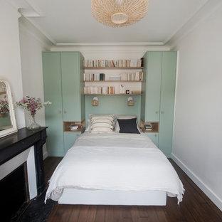 Diseño de dormitorio principal, vintage, de tamaño medio, con paredes multicolor, suelo de madera oscura, chimenea tradicional, marco de chimenea de piedra y suelo marrón