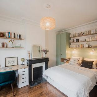 Idée de décoration pour une chambre parentale nordique de taille moyenne avec un mur multicolore, un sol en bois foncé, une cheminée standard, un manteau de cheminée en pierre et un sol marron.