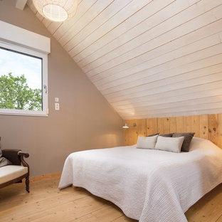 Inspiration pour une chambre mansardée ou avec mezzanine design avec un mur beige et un sol en bois brun.
