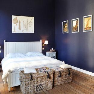 Exemple d'une chambre parentale chic de taille moyenne avec un mur bleu et un sol en bois brun.