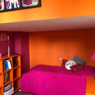 Modelo de habitación de invitados actual, de tamaño medio, sin chimenea, con parades naranjas, suelo de madera clara y suelo gris