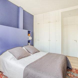 Réalisation d'une chambre design avec un mur violet, un sol en bois clair, aucune cheminée et du papier peint.