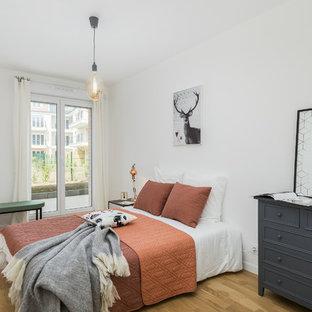 Exemple d'une chambre d'amis scandinave avec un mur blanc, un sol en bois clair et un sol beige.