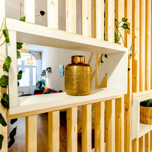 Ejemplo de dormitorio tipo loft, contemporáneo, pequeño, con paredes blancas y suelo de madera clara