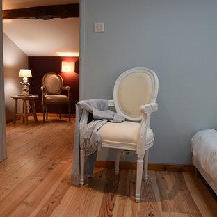 Idee per una camera da letto country con pareti rosse e parquet chiaro