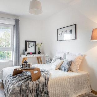 Cette photo montre une chambre d'amis scandinave avec un mur blanc, un sol en bois brun et un sol marron.