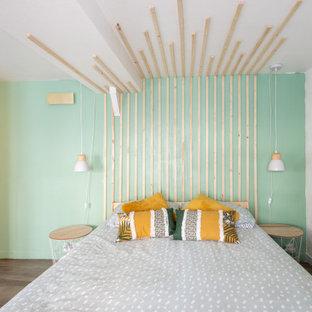 Exempel på ett litet nordiskt huvudsovrum, med gröna väggar, plywoodgolv och brunt golv