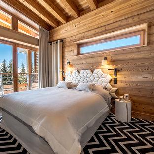 Idée de décoration pour une chambre chalet avec un mur beige et un sol multicolore.