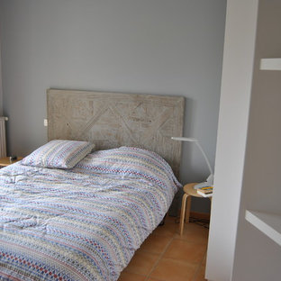 This is an example of a small modern guest bedroom in Rennes with grey walls, terra-cotta floors and no fireplace.
