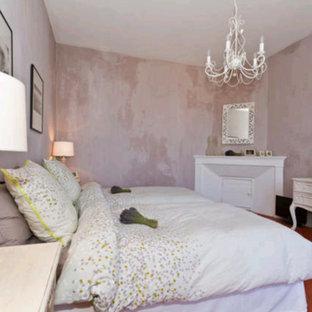 На фото: большая хозяйская спальня в стиле кантри с фиолетовыми стенами, полом из терракотовой плитки, стандартным камином и фасадом камина из штукатурки с
