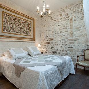 Cette photo montre une chambre parentale chic de taille moyenne avec un sol en bois foncé et un mur beige.