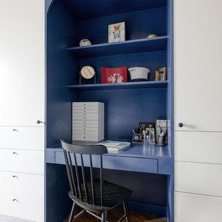 Réalisation d'une chambre parentale design de taille moyenne avec un mur blanc, un sol en bois clair, aucune cheminée, un manteau de cheminée en pierre et un sol marron.