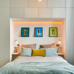 Cette photo montre une chambre scandinave avec un mur gris et un sol en bois clair.