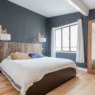 Cette photo montre une grande chambre adulte bord de mer avec un mur bleu, un sol en bois clair et aucune cheminée.