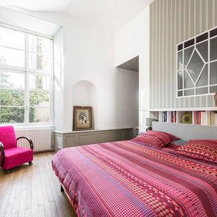 Inspiration pour une chambre d'amis design de taille moyenne avec un mur multicolore et un sol en bois brun.