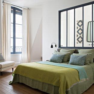 Inspiration pour une chambre parentale design avec un mur blanc, un sol en bois brun et un sol marron.