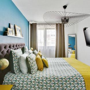 Exemple d'une chambre tendance avec un mur bleu.