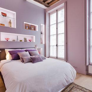 Imagen de dormitorio principal, bohemio, grande, con paredes púrpuras, suelo de madera clara y suelo beige