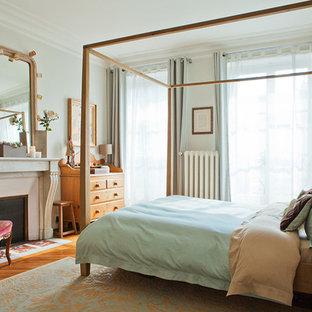 Aménagement d'une grand chambre parentale classique avec un mur gris, une cheminée standard, un sol en bois foncé, un manteau de cheminée en pierre et un sol marron.