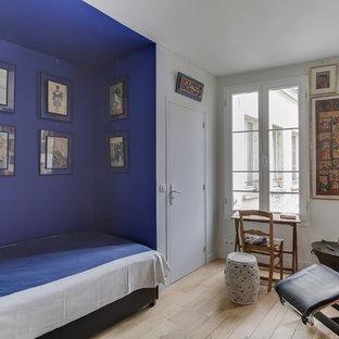 Idée de décoration pour une petit chambre d'amis bohème avec un mur bleu, un sol en bois clair, un sol beige et aucune cheminée.