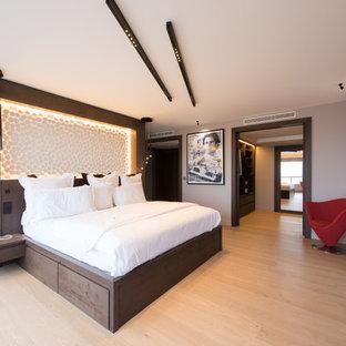 Exemple d'une chambre parentale tendance de taille moyenne avec un mur blanc, un sol en bois clair, aucune cheminée et un sol marron.