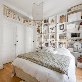 Cette photo montre une chambre parentale éclectique avec un mur blanc, un sol en bois brun et aucune cheminée.