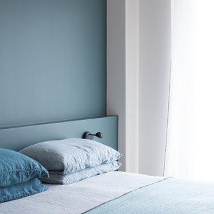 Bild på ett litet skandinaviskt huvudsovrum, med blå väggar och mellanmörkt trägolv