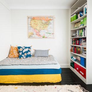 Cette image montre une chambre design avec un mur blanc, un sol en bois peint, aucune cheminée et un sol noir.