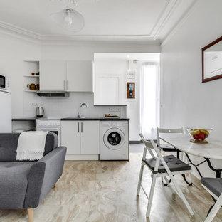 Cette image montre une cuisine ouverte design en L avec un évier posé, un placard à porte plane, des portes de placard blanches, une crédence blanche, un électroménager blanc, un sol beige et un plan de travail noir.