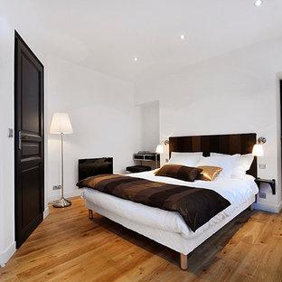 Idées déco pour une chambre parentale classique de taille moyenne avec un mur blanc et un sol en bois brun.