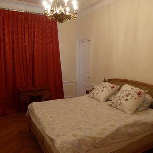 Imagen de dormitorio principal, tradicional renovado, de tamaño medio, con paredes beige, suelo de madera en tonos medios, chimenea tradicional, marco de chimenea de piedra y suelo marrón
