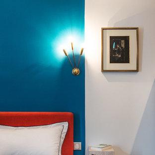 Cette photo montre une chambre tendance avec un mur bleu.