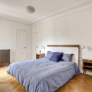 Idées déco pour une chambre scandinave avec un mur blanc et un sol en bois brun.