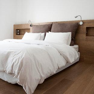 Modelo de dormitorio principal, moderno, de tamaño medio, con paredes blancas y suelo de madera en tonos medios