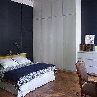 Idée de décoration pour une grand chambre parentale design avec un mur bleu et un sol en bois brun.
