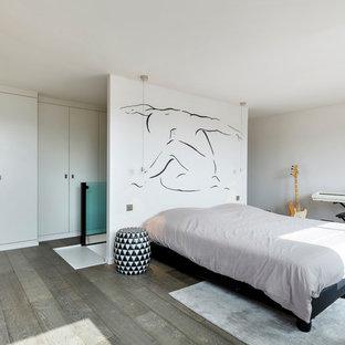 Aménagement d'une grand chambre parentale contemporaine avec un mur blanc, un sol en bois brun et un sol gris.