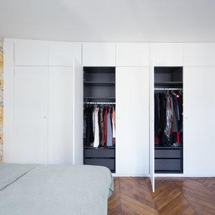 Cette photo montre une chambre tendance avec un sol en bois brun, un sol marron et un mur jaune.