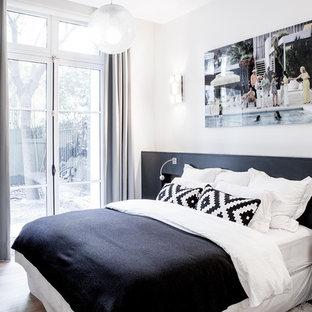 Foto de dormitorio principal, actual, de tamaño medio, sin chimenea, con paredes blancas y suelo de madera en tonos medios