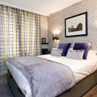 Idée de décoration pour une chambre parentale design de taille moyenne avec un mur blanc et un sol en bois brun.