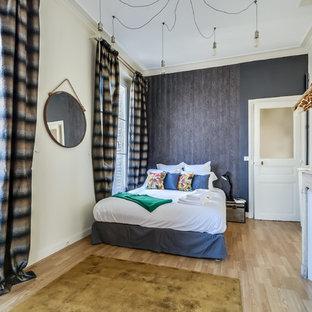 Aménagement d'une grand chambre parentale classique avec un sol en bois clair, une cheminée standard et un mur gris.